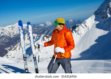 Young man stands with ski in snow and beautiful mountain view on background in sunny weather on Krasnaya polyana, Sochi