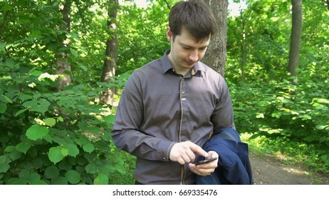 Young man stands in the woods, thinks about something and works on the phone.