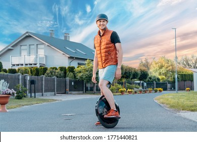 Young Man Stanging On Electric Unicycle (EUC) On Street, Best Mobile Portable Personal Transportation Vehicle, Summer Day -  Riga / Latvia - June 1st 2020