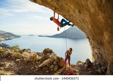 Young man starts climbing challenging route in cave, his female partner belaying him