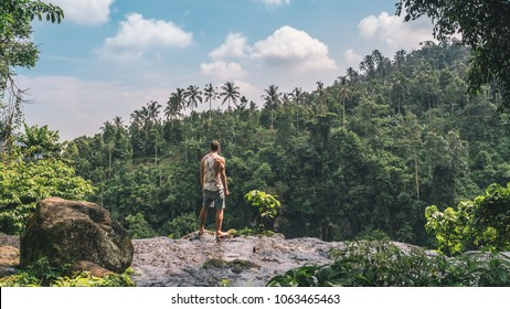 Young man staying on the edge of waterfall in jungles in Bali island in Indonesia. Lots of palms and blue sky on the background.