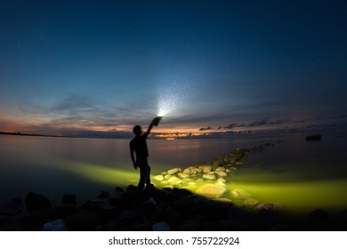A young man staying on the stone breakwater line and holding very powerful torch