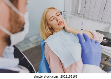 Young man stomatologist doctor in mask hold syringe going to make injection anesthesia for suffering patient sad woman with caries sit at dentist office chair indoor cabinet Healthcare decay treatment
