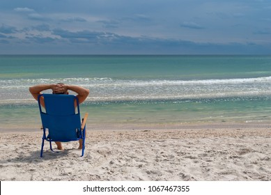 young man in a straw hat sits on the seashore from the back, summer beach waves sky with clouds, sand, sits in a deckchair throwing his hands behind his head and looking at the horizon, resting