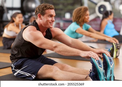 Young man stretching in a gym