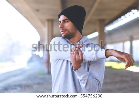 Young man stretching his arm muscles under the bridge before running.