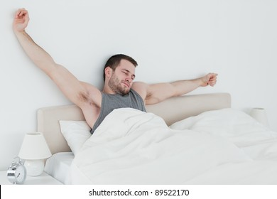 Young man stretching his arms in his bedroom