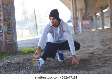 Young man stretching his leg muscles under the bridge before running.