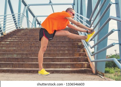 Young man stretching on a fence after jogging / excercising.