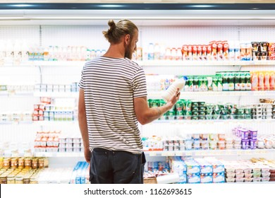 Young man in striped T-shirt thoughtfully choosing milk in dairy department of modern supermarket