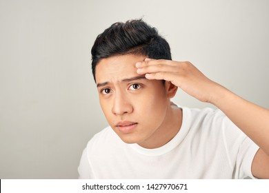 Young man struggling with acne on his face caring for his skin pushes acne