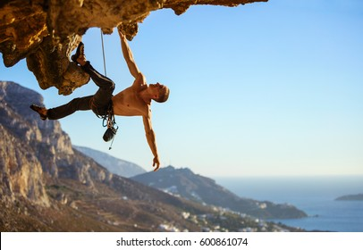 Young man struggling to climb ledge on cliff, view of coast below