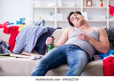Young man student drunk drinking alcohol in a messy room