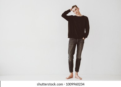 A young man, a student stands against a white wall in the room, dressed in short jeans and a black sweater, barefoot. The guy is a model.