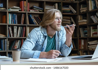Young man student teacher holding mobile speak activate virtual digital voice recognition assistant on smart phone record message studying sit in library, mobile app ai internet technology concept