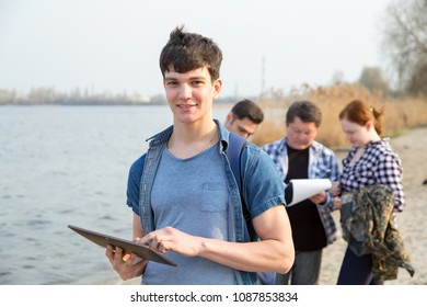 Young man student is working on a digital tablet. Employee team of an environ mentalist on the background of a working group of men. Ecologists are studying the pollution of the reservoir.