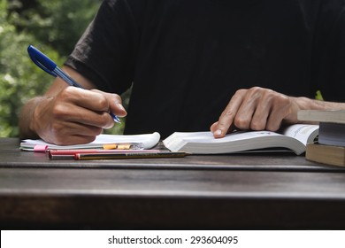 young man studing and taking notes