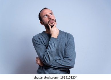 young man in studio thinking and looking toward the sky or the ceiling with thoughtful expression. pondering and imagining with hand on the chin. concentrated man on white background. copy space