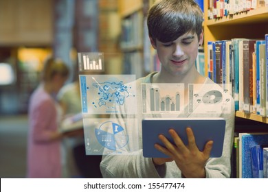 Young man studying on his digital tablet computer in a library