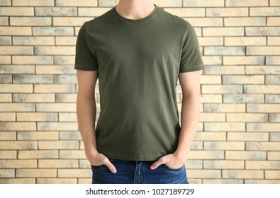 Young man in stylish t-shirt against brick wall. Mockup for design