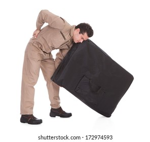 Young Man Suffering From Back Pain Lifting Luggage Over White Background