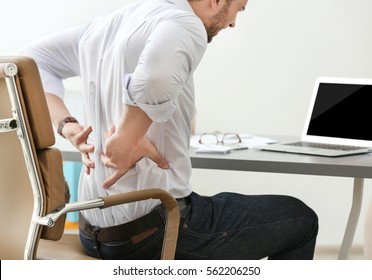 Young man suffering from backache in office, closeup