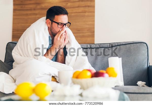 自宅で風邪をひいている青年