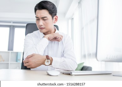 Young man suffering from elbow pain in office