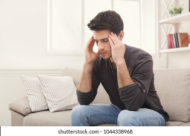 Young man suffering from headache after hard working day, sitting on couch at home, copy space