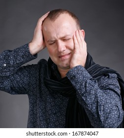 Young man suffering from  headache on a gray background