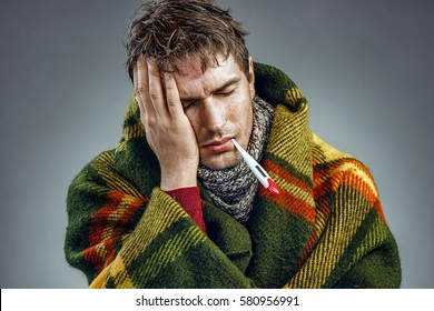 Young man suffering from a headache. Photo of sick man wrapped in blanket with a thermometer in his mouth.