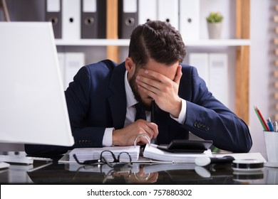 Young Man Suffering From Headache Working In Office With Bill Over Desk