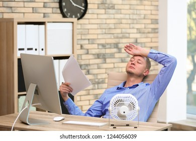 Young man suffering from heat in front of small fan at workplace