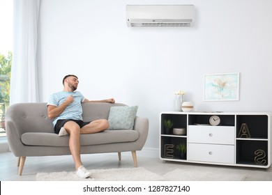 Young man suffering from heat near broken air conditioner at home