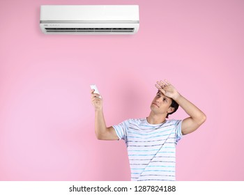 Young man suffering from heat and turning on air conditioner against color background