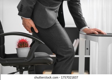 Young man suffering from hemorrhoids in office