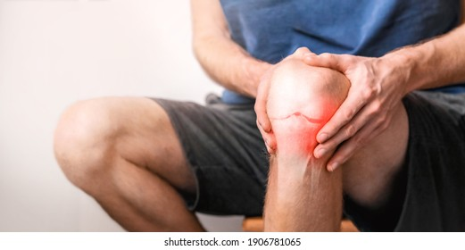 Young man suffering from knee pain at home, close up.  Joint inflammation concept.