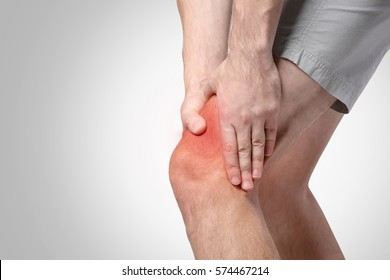 Young man suffering from knee pain on light background. Health care concept