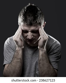 young man suffering migraine and headache in intense pain feeling desperate and sick with hands on tempo in stress isolated on black studio background