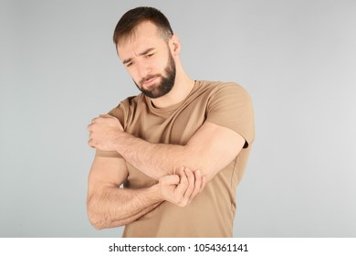 Young man suffering from pain in elbow on light background