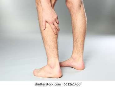 Young man suffering from pain in leg on grey background