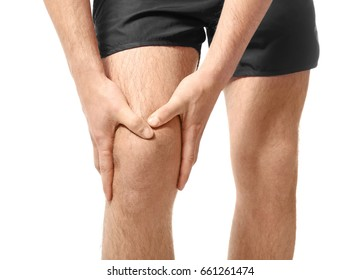 Young man suffering from pain in leg on white background, closeup