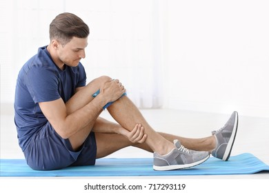 Young man suffering from pain in leg at home
