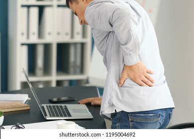 Young man suffering from pain in office