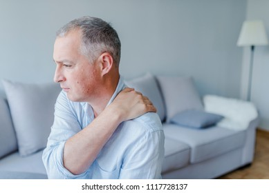 Young man suffering from pain in shoulder, closeup.People, healthcare and problem concept - unhappy man suffering from neck or shoulder pain at home. Shoulder pain Caused by not taking care of health.