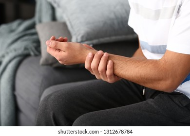 Young man suffering from pain in wrist at home, closeup