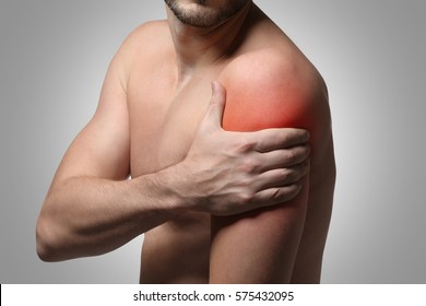 Young man suffering from shoulder pain on gray background. Health care concept