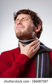 Young man suffering from sore throat, vertical