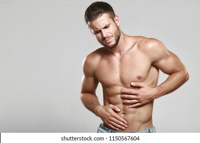Young man suffering from stomach ache. Causes of abdominal pain include gastritis, stomach ulcer, food poisoning, diarrhea or IBS. Gray background. Healthcare, medical and sickness concept.