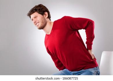 Young man suffering from strong backache, horizontal